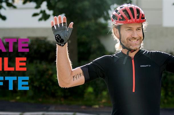 Syklist med hendene opp.